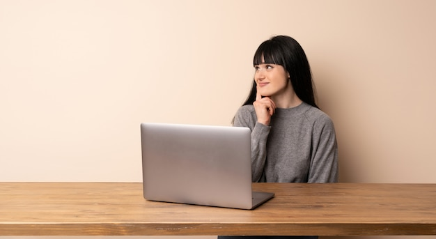 Young woman working with her laptop thinking an idea while looking up Premium Photo
