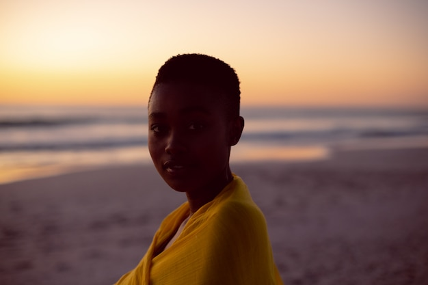 Young woman wrapped in yellow scarf on the beach Free Photo