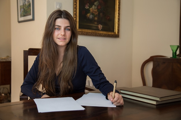 Young woman writing on a blank sheet with a pen. Premium Photo