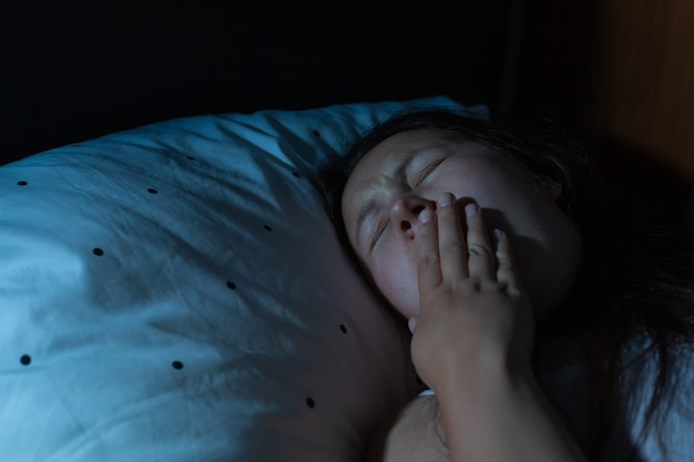 Young woman yawning, suffering from the chronic insomnia, sleep disorder Premium Photo