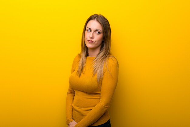Young woman on yellow background feeling upset Premium Photo