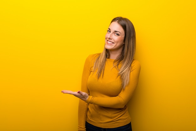 Young woman on yellow background presenting an idea while looking smiling towards Premium Photo