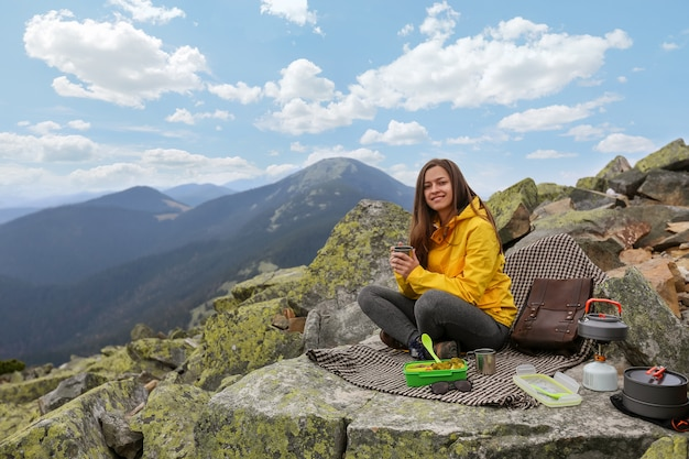 Young woman in yellow jacket have a picnic on top of the mountain. Premium Photo