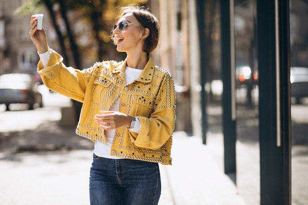 Young woman in yellow jacket using phone outside in the street Free Photo