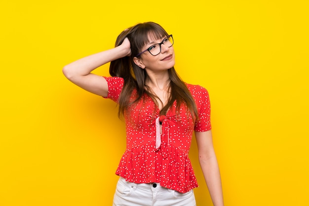 Young woman over yellow wall thinking an idea Premium Photo
