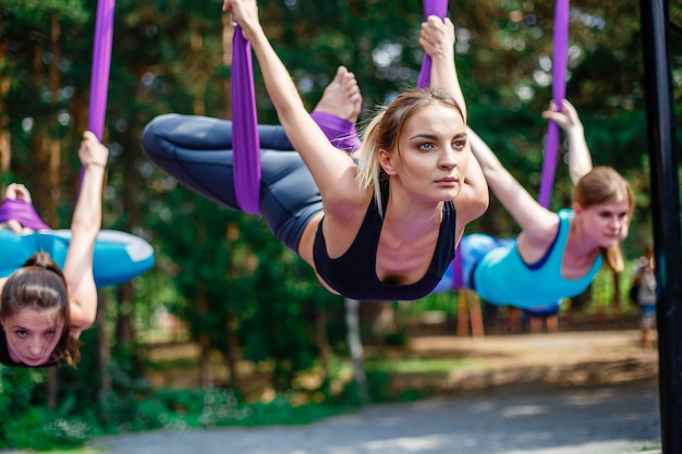 Young women, antigravity yoga exercises with a group of people outdoors. Premium Photo