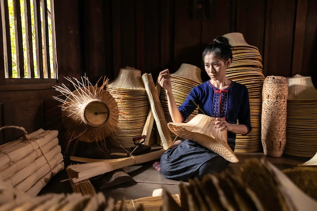 Young women are weaving in field handmade basket of thailand. Premium Photo