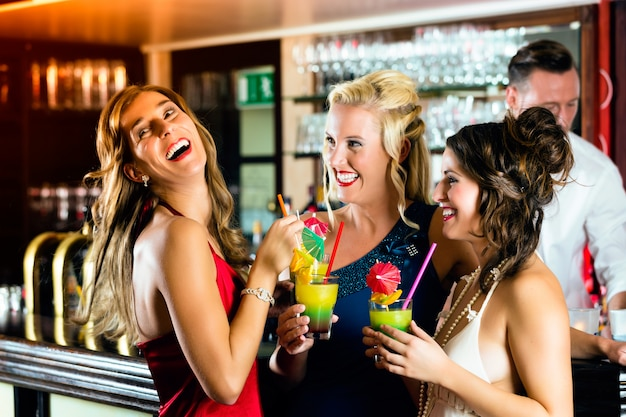 Young women in bar or club having fun and laughing Premium Photo