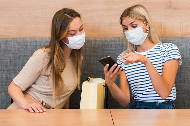 Giovani donne che controllano insieme il telefono cellulare Foto Gratuite