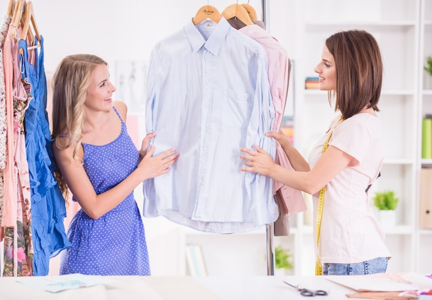 Young women choosing clothes on a rack in a showroom. Premium Photo