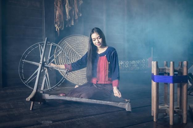 Young women demonstrate to procedure of making thai silk weaving in thailand Premium Photo