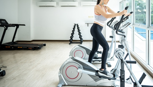 Young women doing sport biking  with her friend in the gym for fitness Premium Photo