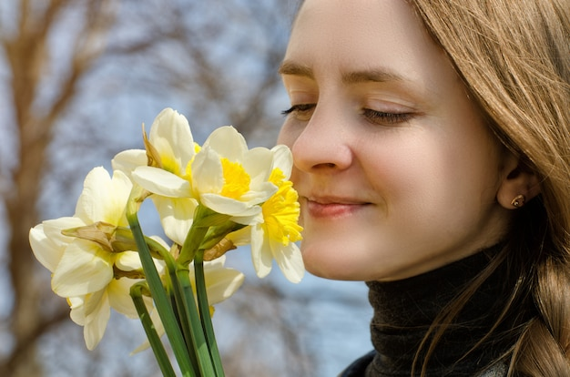 Young women enjoy the bouquet of daffodils, close-up Premium Photo