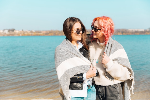 Young women hugging and covering with blanket Free Photo