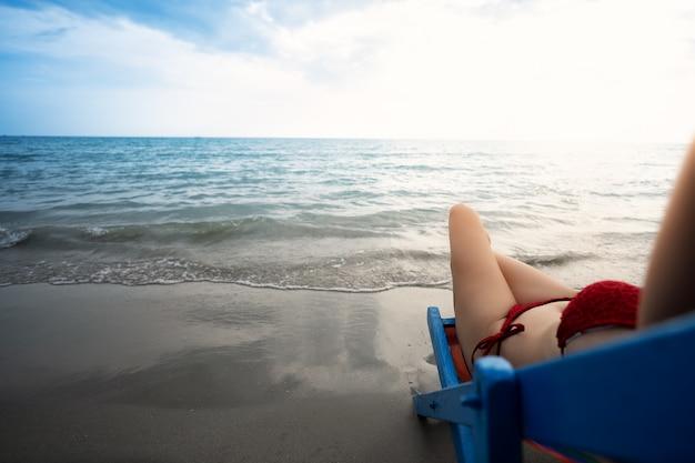 Молодые женщины в бикини отдыхают на пляже Premium Фотографии