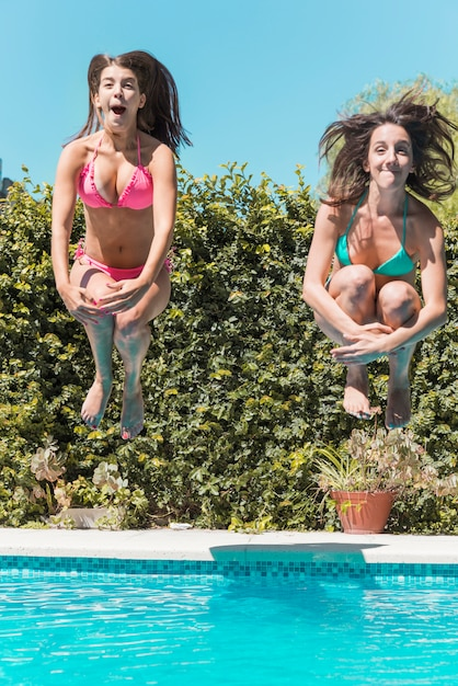 Young women jumping in swimming pool Free Photo