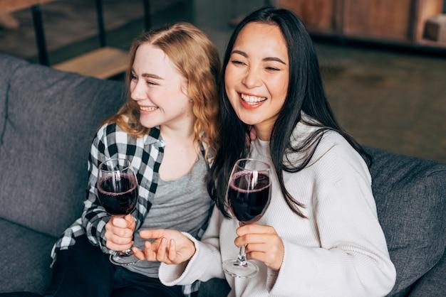 笑いとワインを飲む若い女性 無料写真