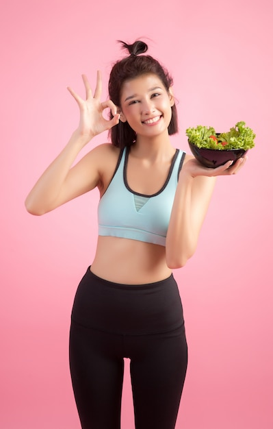 Young women like to eat vegetables on a pink. Free Photo