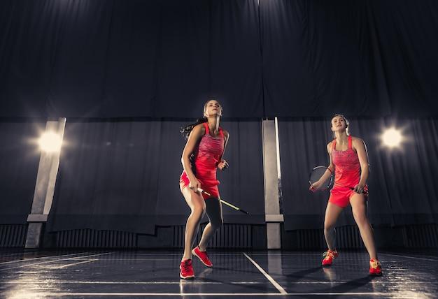 Молодые женщины играют в бадминтон в тренажерном зале Бесплатные Фотографии