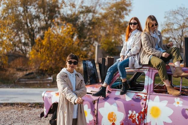 오래 된 장식 된 자동차 근처 포즈 젊은 여성 무료 사진