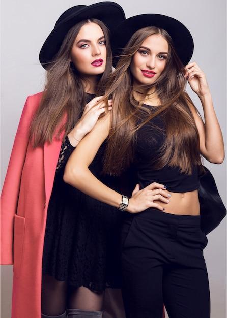 Young women posing and wearing stylish black hats Free Photo
