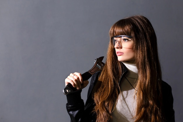 Young women in protective glasses with adjustable wrench on a dark Premium Photo