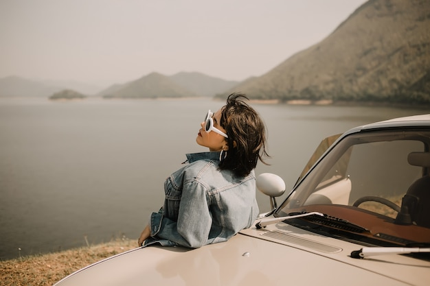 Young women relaxing on lake. she go to lake by classic car. she wearing sunglasses. Premium Photo