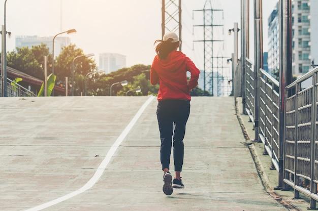 路上で若い女性ランナーが市の道路で運動をしている。スポーツ、人々、運動、ライフスタイルコンセプト Premium写真