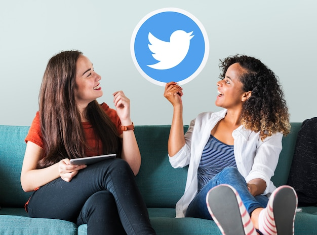 Young women showing a twitter icon Free Photo