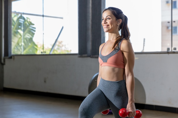 Young women in sportswear doing exercise with dumbbells in gym. Premium Photo