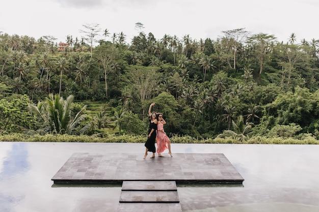 Giovani donne in piedi davanti alla giungla. colpo integrale all'aperto di bei modelli femminili vicino al lago nel paese esotico. Foto Gratuite