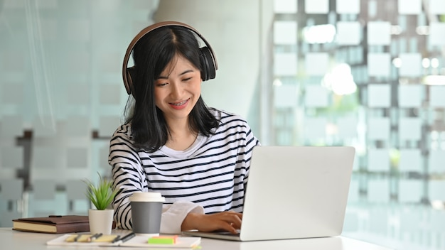 Young women using laptop and listening song in headphones Premium Photo