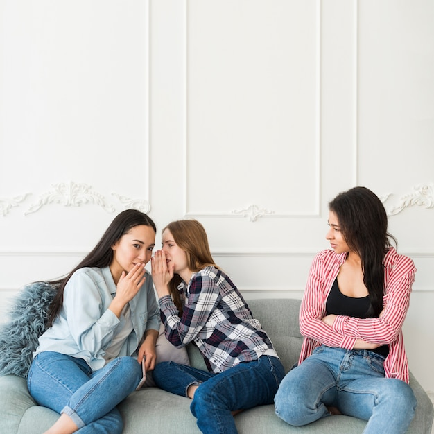 Young women whispering behind friend Free Photo