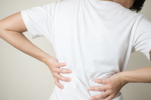 Young women with muscular pain in her back, caused by heavy lifting, spinal diseases. Premium Photo