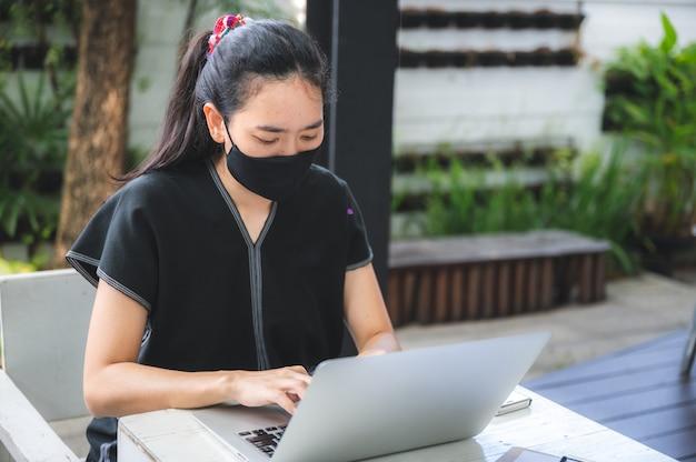 ラップトップで自宅からビジネスを働く若い女性 Premium写真
