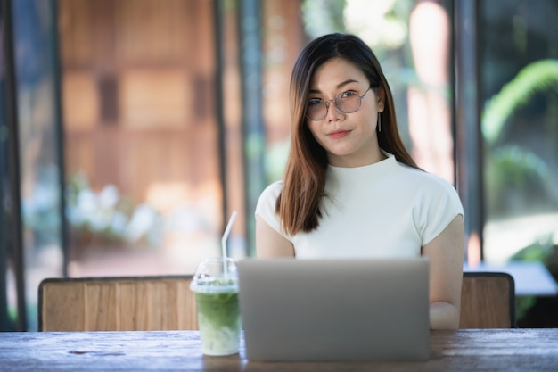 Young women working with laptop on the wood table in the cafe, business concept Premium Photo