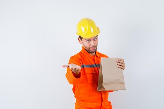 紙袋を持って、制服を着て手を伸ばしている若い労働者。 無料写真
