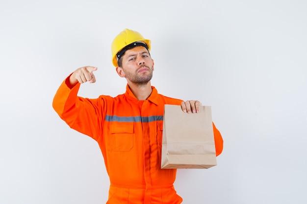 正面を向いて、紙袋を持って制服を着た若い労働者。 無料写真