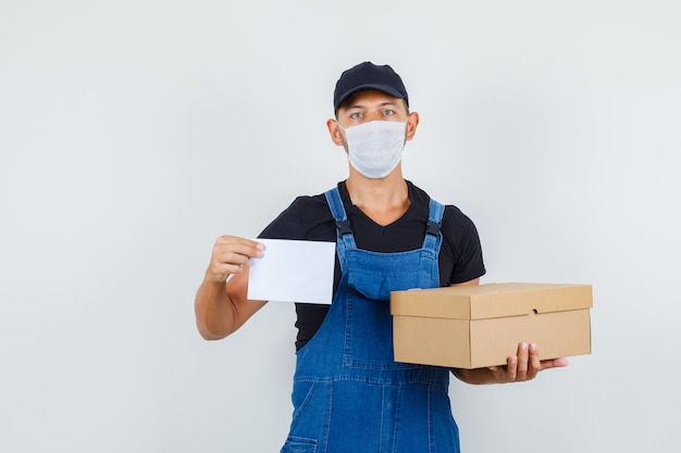 골 판지 상자와 종이 시트, 전면보기를 들고 유니폼, 마스크에 젊은 노동자. 무료 사진