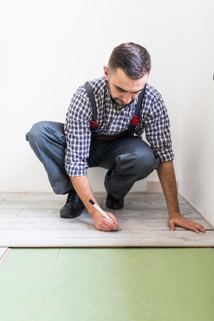 Giovane operaio che riveste un pavimento con assi del pavimento laminato Foto Gratuite
