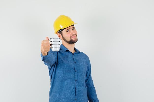 シャツ、ヘルメットで一杯のコーヒーを提供し、優しく見える若い労働者 無料写真