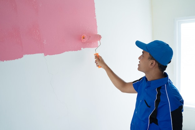Young worker painting on the wall Premium Photo