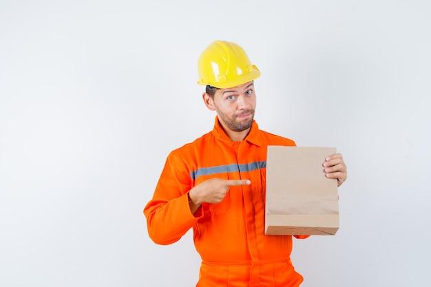 制服、ヘルメットの紙袋を指している若い労働者。 無料写真