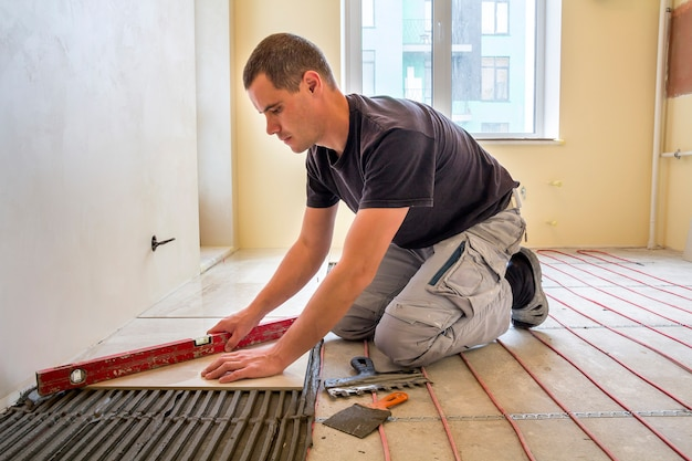 Young worker tiler installing ceramic tiles using lever on cement floor with heating red electrical cable wire system. home improvement, renovation and construction, comfortable warm home concept. Premium Photo