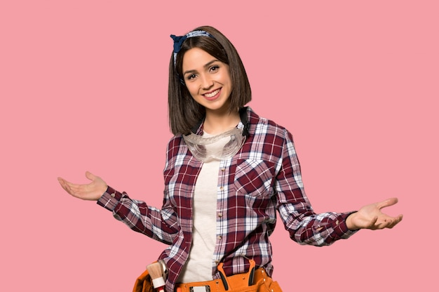 Young worker woman proud and self-satisfied on isolated pink wall Premium Photo