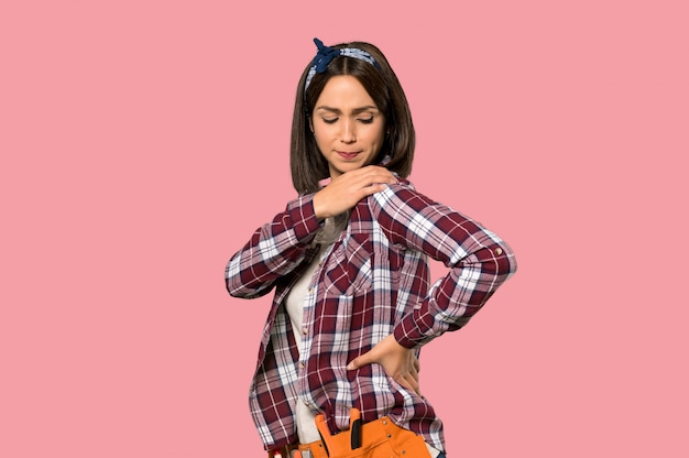 Young worker woman suffering from pain in shoulder for having made an effort on isolated pink wall Premium Photo