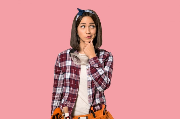 Young worker woman thinking on isolated pink wall Premium Photo