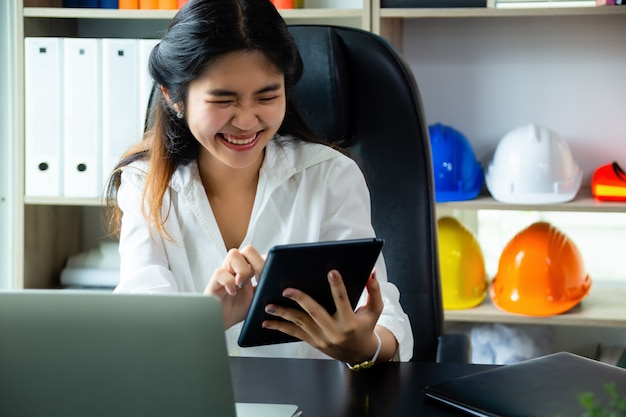 Young working woman enjoy to use tablet in office Free Photo