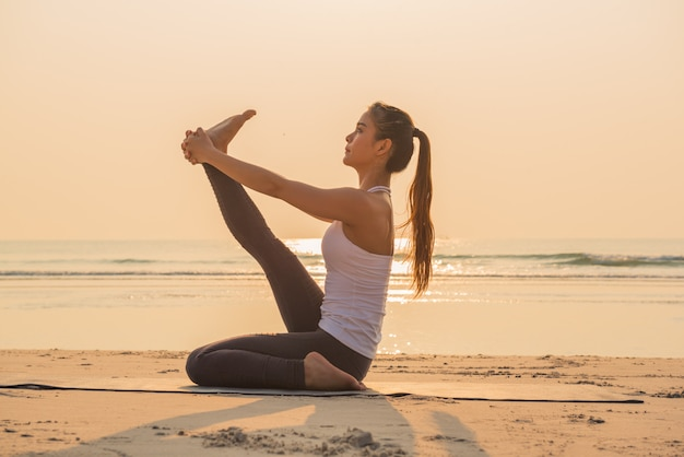 Young yoga woman stretching leg on the beach Premium Photo