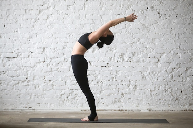 Young yogi attractive woman in ardha chakrasana pose, loft backg Free Photo